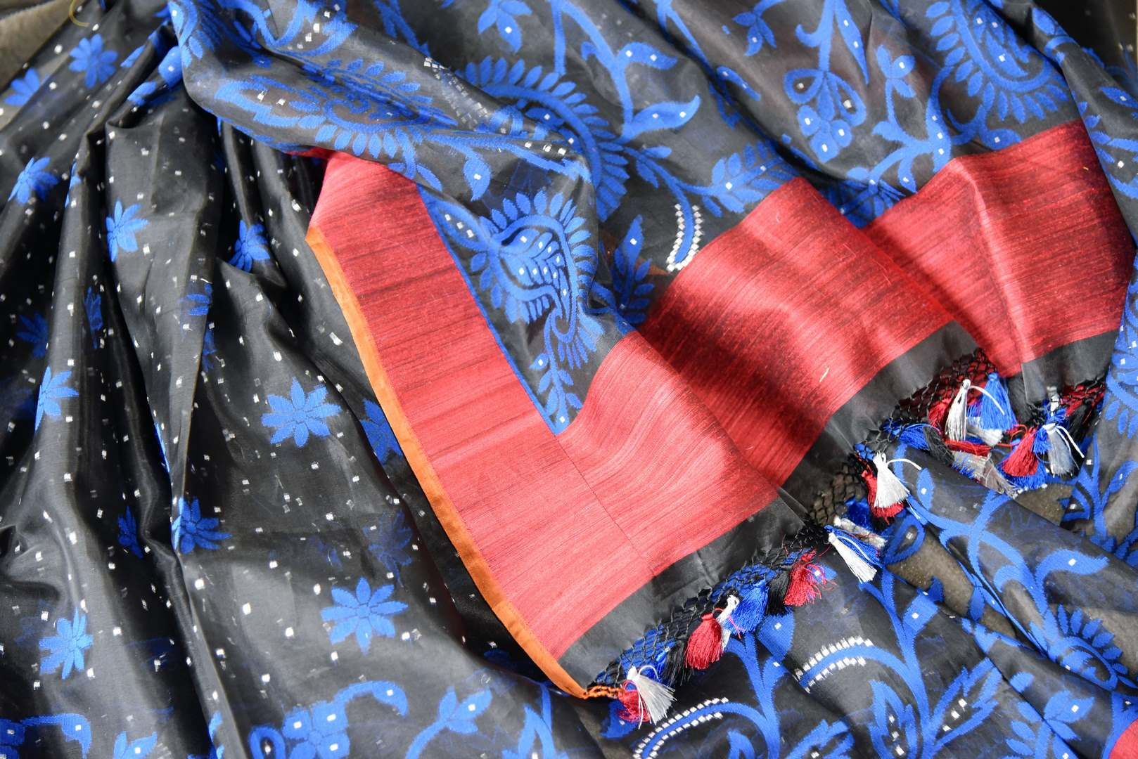 Channel contemporary vibes in this exclusively designed black kora tissue silk with banarsi weave. It comes with a red silk contrasting border and floral work. Style this sari with red and black silk blouse. Shop handloom saris, chiffon sarees, printed sari online or visit Pure Elegance store, USA.-details