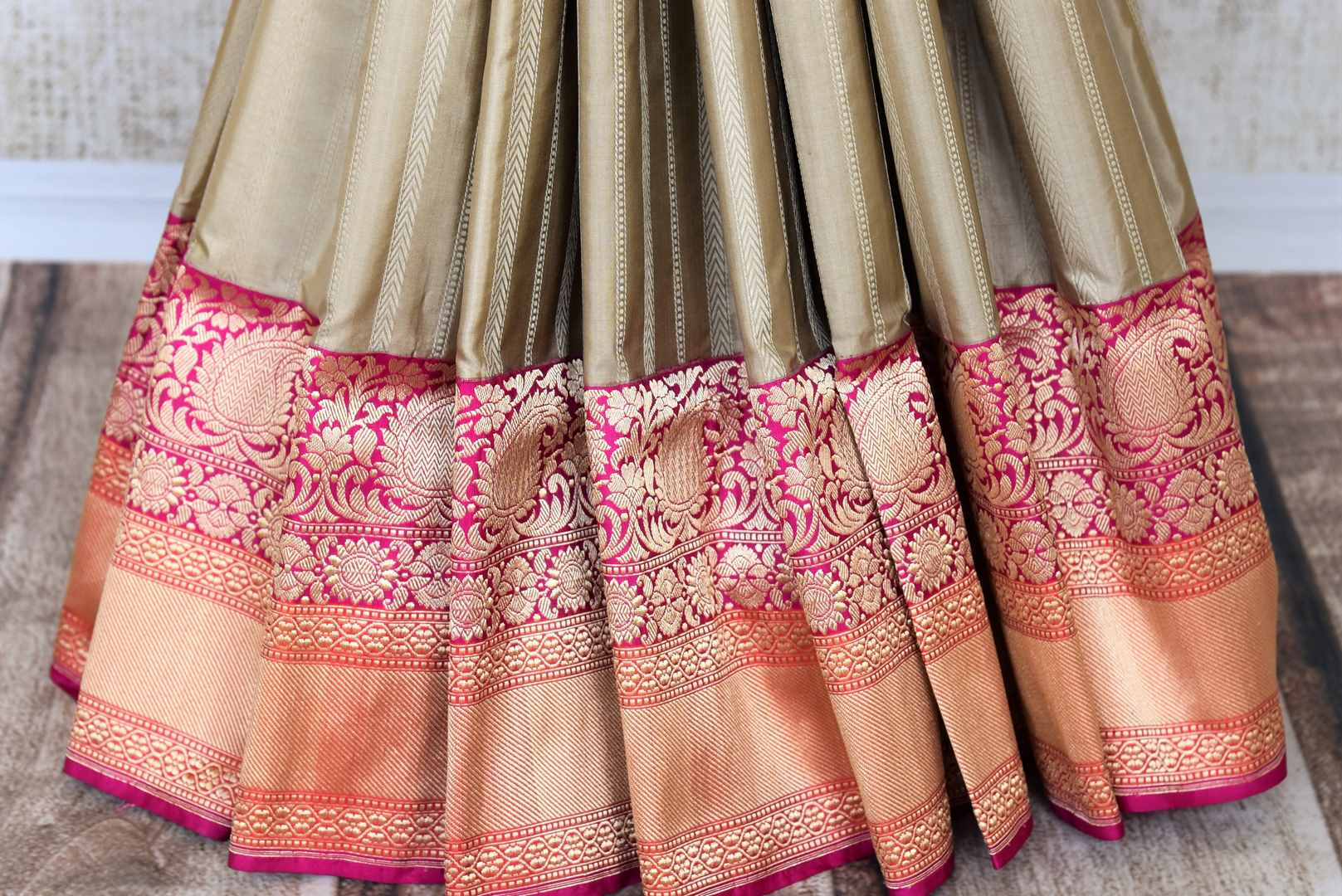 Unleash the Bollywood diva in you in this sartorial designer cream banarsi silk sari. Drape this gorgeous saree with designer fuschia and gold buta work blouse to enhance the royalty in you. Shop designer silk Indian sarees, banarasi silk sarees, georgette sarees online or visit Pure Elegance store in USA. -pleats