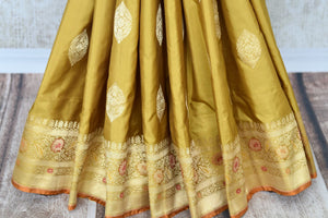 Rich gold Banarasi silk saree buy online in USA with zari buta and border. The saree is sure to bring splendor to your Indian wedding look. If you are looking for Indian designer silk sarees, Banarasi sarees in USA, then Pure Elegance clothing store is your one-stop solution, shop now.-pleats
