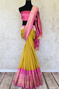 Leave them awestruck as you dress up in our exclusively designed yellow organza banarsi silk saree. It features a graceful pink pallu and contrasting pink buta work designer blouse. Shop designer silk saris, kanjeevaram silk saris, printed sarees online or visit Pure Elegance store in the USA.-full view