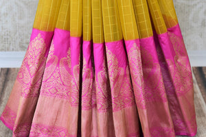 Leave them awestruck as you dress up in our exclusively designed yellow organza banarsi silk saree. It features a graceful pink pallu and contrasting pink buta work designer blouse. Shop designer silk saris, kanjeevaram silk saris, printed sarees online or visit Pure Elegance store in the USA.-pleats