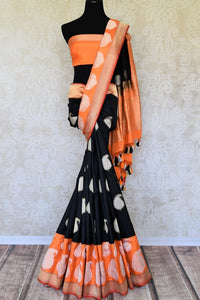 Escalate your fashion game in this spectacular black banarsi silk designer saree. Style this designer silk sari with a contrast orange blouse with zari detailing and heavy rich gold embroidered pallu. Shop silk sarees, printed sarees, handloom saris online or visit Pure Elegance store, USA. -full view