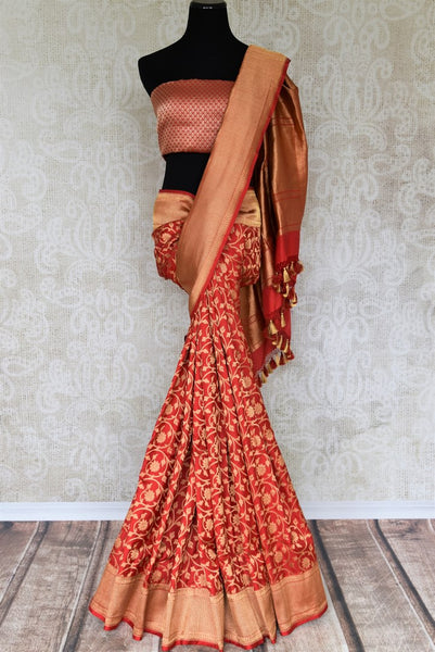 A classic amalgamation of red and gold blended seamlessly in this designer banarsi silk sari. A rich gold floral work all over, contrasting red zari blouse and heavily woven pallu makes it perfect for Indian brides. Shop designer silk saris, embroidery sarees, Indian dresses online or visit Pure Elegance, USA.-full view