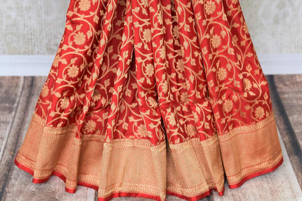 A classic amalgamation of red and gold blended seamlessly in this designer banarsi silk sari. A rich gold floral work all over, contrasting red zari blouse and heavily woven pallu makes it perfect for Indian brides. Shop designer silk saris, embroidery sarees, Indian dresses online or visit Pure Elegance, USA.-pleats