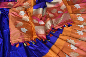 Flawlessly designed blue banarsi silk saree with a stunning combination of orange buta work border, it is perfect for parties, weddings and formal events. Style this sari with a rich silk orange blouse to ooze the sass. Shop handcrafted silk sarees, designer sari, printed saris online or visit Pure Elegance store, USA.-details