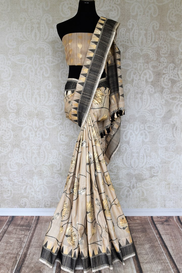 Shop artistically designed cream Tussar Banarasi silk saree with quirky tassel drops on the pallu. Invest in authentic silk sari and complement with a stunning designer blouse to turn heads effortlessly. Shop handloom sarees, designer Indian silk saris online or visit Pure Elegance store in USA. -full view