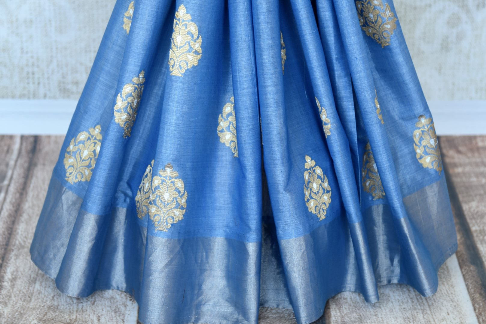 Escalate your style game in this stunning blue linen silk saree with intricate buta work. The dull gold buta work all over the saree with a heavily woven pallu is a perfect ensemble when styled with blue and gold silk blouse. Shop handloom saris, silk saree, printed saree online or visit Pure Elegance store, USA.-pleats