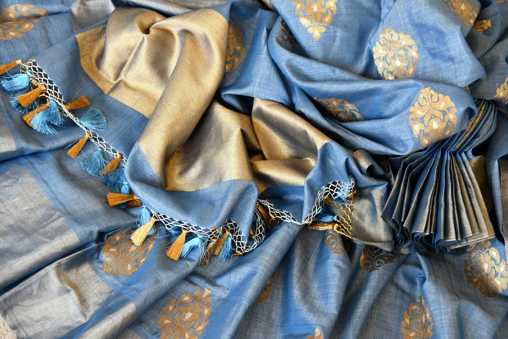 Escalate your style game in this stunning blue linen silk saree with intricate buta work. The dull gold buta work all over the saree with a heavily woven pallu is a perfect ensemble when styled with blue and gold silk blouse. Shop handloom saris, silk saree, printed saree online or visit Pure Elegance store, USA.-details
