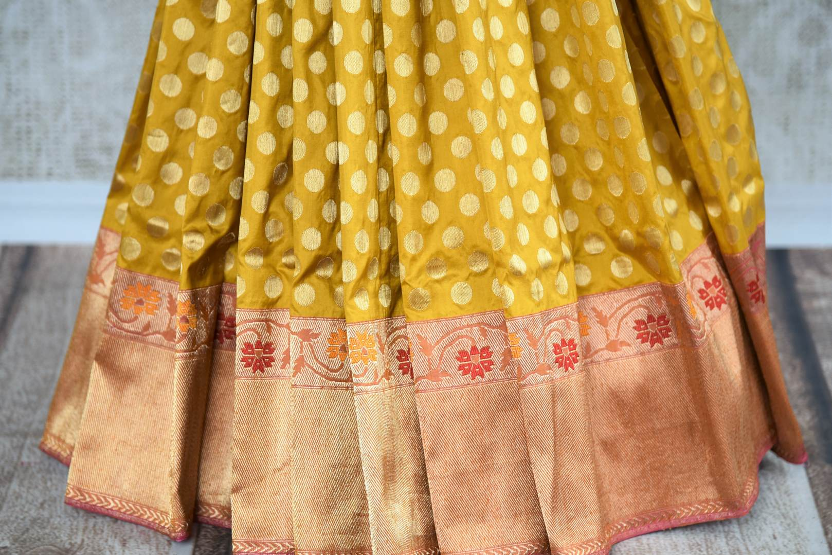 Buy online yellow Banarasi silk saree in USA with zari border. The saree is a rich drape for a traditional wedding look. If you are looking for Indian handloom sarees, Banarasi silk saris in USA, then Pure Elegance is the place for you. Shop online or visit our exclusive fashion store in USA.-pleats