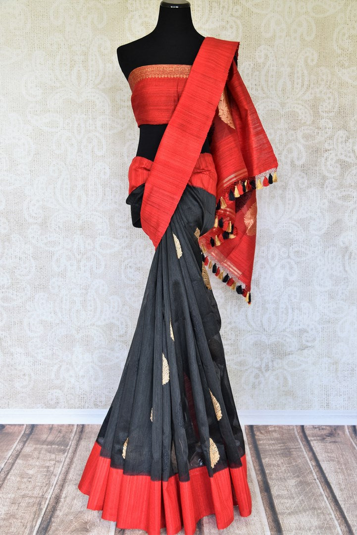 The signature combination of black and red blended in this designer kora banarsi silk saree is quite a treat for women. Strike a lasting impression with the red zari detailed blouse and heavily woven pallu. Shop handcrafted silk saris, georgette saris, ikkat sarees online or visit Pure Elegance store, USA. -full view