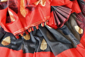 The signature combination of black and red blended in this designer kora banarsi silk saree is quite a treat for women. Strike a lasting impression with the red zari detailed blouse and heavily woven pallu. Shop handcrafted silk saris, georgette saris, ikkat sarees online or visit Pure Elegance store, USA. -details