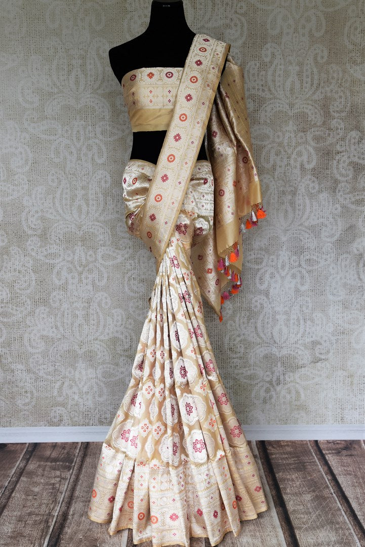 An epitome of grace and poise, this white banarsi silk sari featuring a beautiful floral embroidery is magnificent. It comes with a royal designer blouse and a heavily embroidered pallu. Shop such handcrafted silk saris, printed sarees, kanjeevaram silk sarees, Indian dresses online or visit Pure Elegance store in USA.-full view