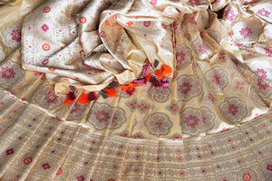 An epitome of grace and poise, this white banarsi silk sari featuring a beautiful floral embroidery is magnificent. It comes with a royal designer blouse and a heavily embroidered pallu. Shop such handcrafted silk saris, printed sarees, kanjeevaram silk sarees, Indian dresses online or visit Pure Elegance store in USA.-details
