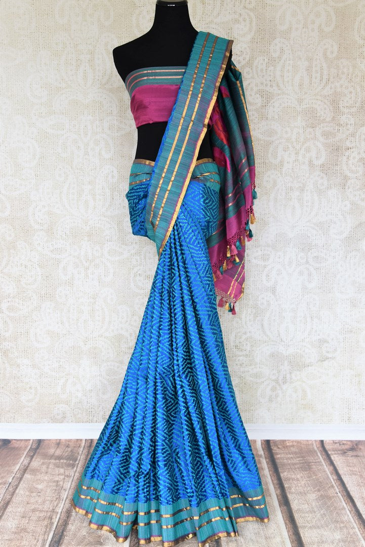Luxe and lavish, this green banarsi silk saree with stunning zari detail looks flamboyant. Style this sari with a pretty pink silk blouse and enhance your look with heavily woven pallu and blue threadwork all over the saree. Shop handloom sarees, linen saris, ikkat sarees online or visit Pure Elegance store, USA.-full view