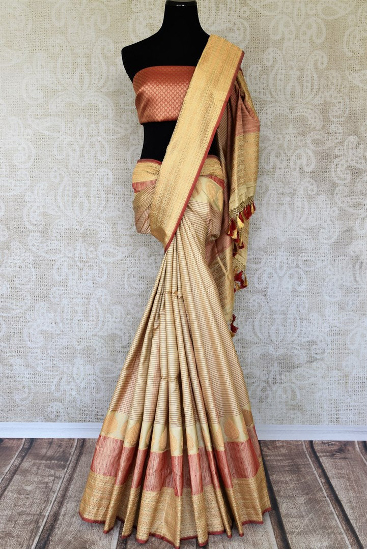 Embrace the traditional banarsi silk sari in white and red hues. Slip into this vibrant designer saree to steal the hearts away at weddings and parties. Pair this with red and gold embroidered blouse. Shop such handloom sari, silk saree, printed sarees online or visit Pure Elegance store, USA. -full view