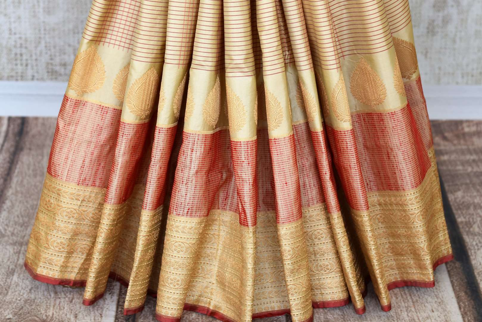 Embrace the traditional banarsi silk sari in white and red hues. Slip into this vibrant designer saree to steal the hearts away at weddings and parties. Pair this with red and gold embroidered blouse. Shop such handloom sari, silk saree, printed sarees online or visit Pure Elegance store, USA. -pleats