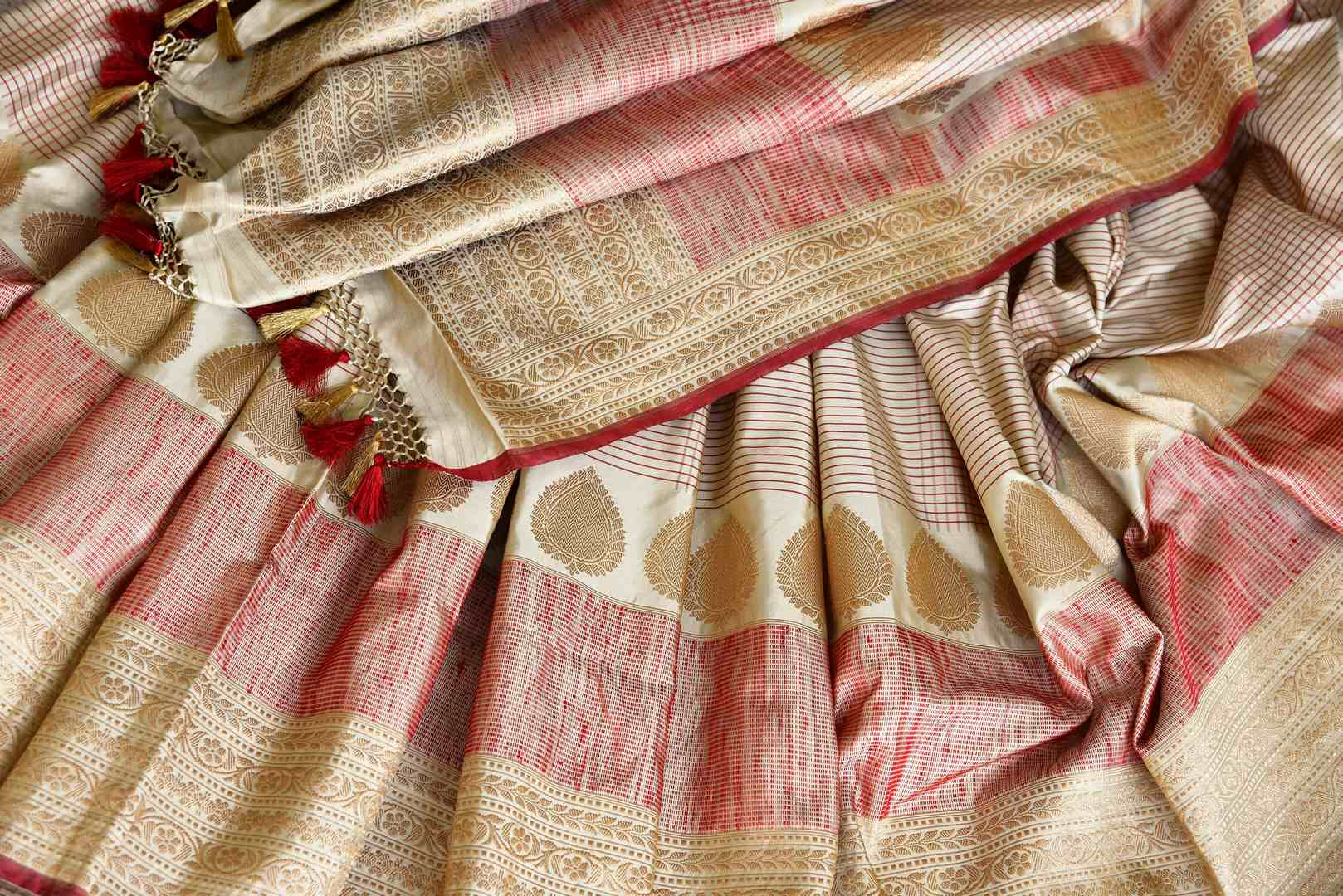 Embrace the traditional banarsi silk sari in white and red hues. Slip into this vibrant designer saree to steal the hearts away at weddings and parties. Pair this with red and gold embroidered blouse. Shop such handloom sari, silk saree, printed sarees online or visit Pure Elegance store, USA. -details
