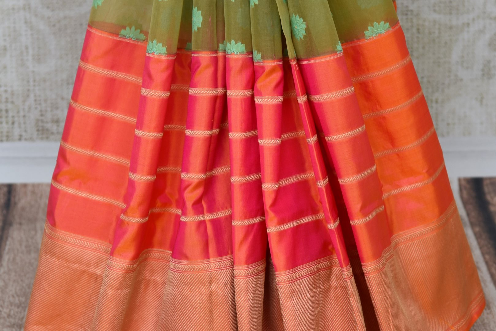Buy green organza Banarasi saree online in USA with pink zari border. The saree is an elegant choice for parties and special occasions. If you are looking for Indian designer sarees, Banarasi silk sarees in USA, then Pure Elegance clothing store is your one-stop solution, shop now.-pleats