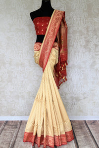 Classics like this white banarasi silk saree comes with a contrasting red designer buta work blouse and heavily embroidered red pallu. The graceful sari can be worn at upscale parties, weddings and festivities. Shop designer printed saris, ikkat saris, handwoven sarees online or visit Pure Elegance store, USA. -full view