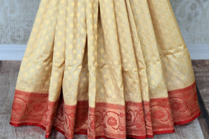 Classics like this white banarasi silk saree comes with a contrasting red designer buta work blouse and heavily embroidered red pallu. The graceful sari can be worn at upscale parties, weddings and festivities. Shop designer printed saris, ikkat saris, handwoven sarees online or visit Pure Elegance store, USA. -pleats
