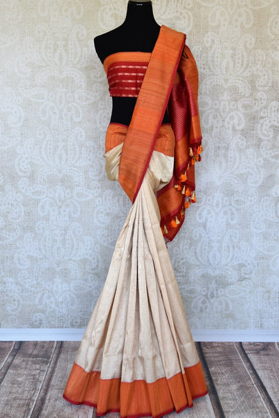Up your fashion game with our exquisitely designed white banarsi silk tissue saree. Featuring elaborate orange border and a stunning woven pallu, this sari works well for parties, weddings and special occasions. Shop handcrafted silk sarees, designer linen sari, printed saree online or visit Pure Elegance store, USA. -full view
