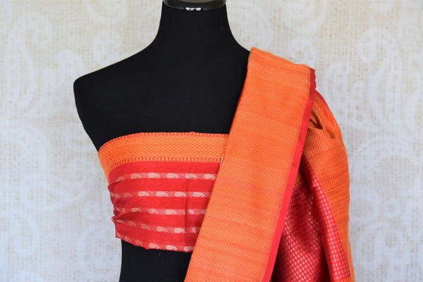 Up your fashion game with our exquisitely designed white banarsi silk tissue saree. Featuring elaborate orange border and a stunning woven pallu, this sari works well for parties, weddings and special occasions. It comes with a deeply enriching red and orange zari detailed designer blouse to notch up your style quotient.-blouse pallu