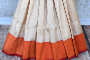 Up your fashion game with our exquisitely designed white banarsi silk tissue saree. Featuring elaborate orange border and a stunning woven pallu, this sari works well for parties, weddings and special occasions. It comes with a deeply enriching red and orange zari detailed designer blouse to notch up your style quotient.-pleats