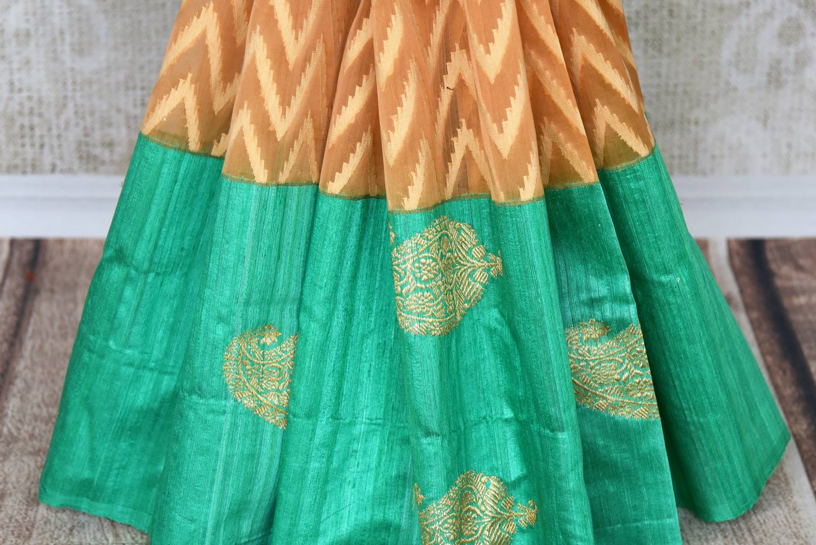 Drape this gorgeous orange organza banarsi silk saree to fancy parties, gala soirees, weddings etc. It comes in a striking green contrast with buta work and paired with visually appealing green buta work blouse. Shop designer silk sari, printed saree, embroidered saree online or visit Pure Elegance store, USA. -pleats