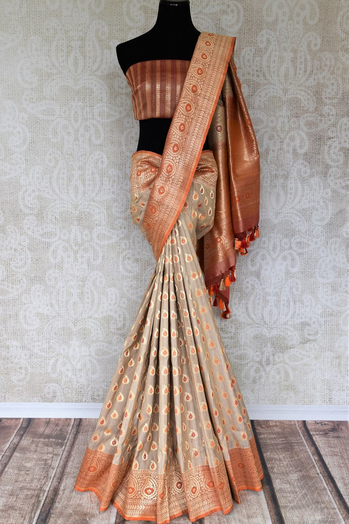 Look resplendent in this subtle cream tussar khaddi banarsi silk saree with intricate buta work all-over. It comes with a rich embroidered pallu and gold designer blouse. Shop designer silk saris, lehenga cholis, anarkali suits, ikkat sarees online or visit Pure Elegance store, USA. -full view