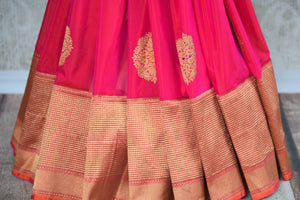 Buy online bright pink Banarasi silk saree in USA with zari border. The saree is a rich drape for a traditional wedding look. If you are looking for Indian handloom sarees, Benarasi  sarees in USA, then Pure Elegance is the place for you. Shop online or visit our exclusive fashion store in USA.-pleats