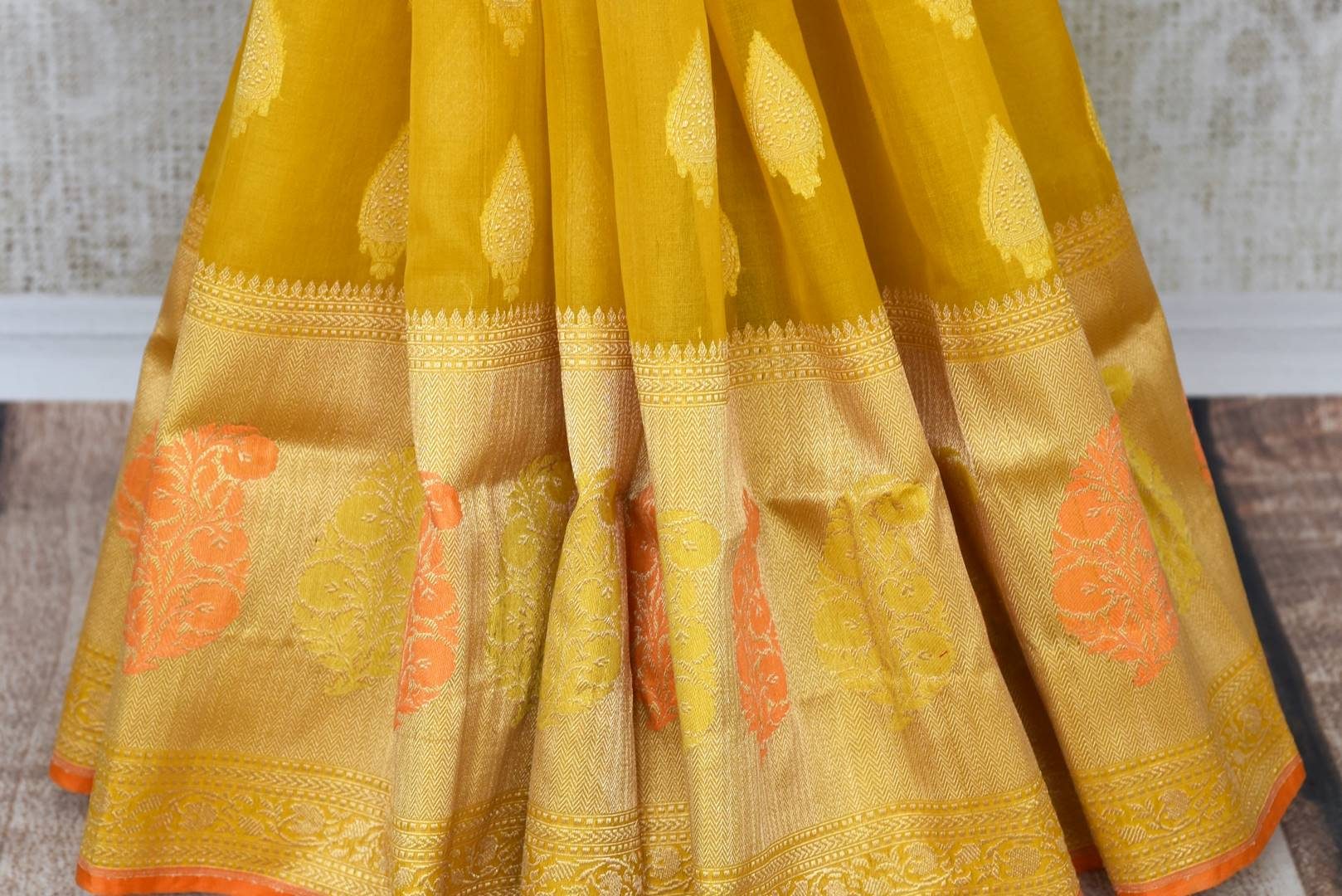 Buy mustard yellow organza Banarasi saree online in USA with zari buta. The saree is a rich drape for weddings and special occasions. If you are looking for Indian designer silk sarees, Banarasi sarees in USA, then Pure Elegance clothing store is your one-stop solution, shop now.-pleats