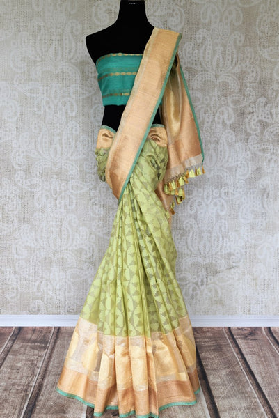 Exquisitely designed, this soft green tissue banarasi silk sari is handwoven with gold buta work all over. It comes with a sea green threadwork blouse curated in 100% silk. Shop beautiful handwoven silk saris, ikkat sarees, georgette saris online or visit Pure Elegance store in USA. -full view