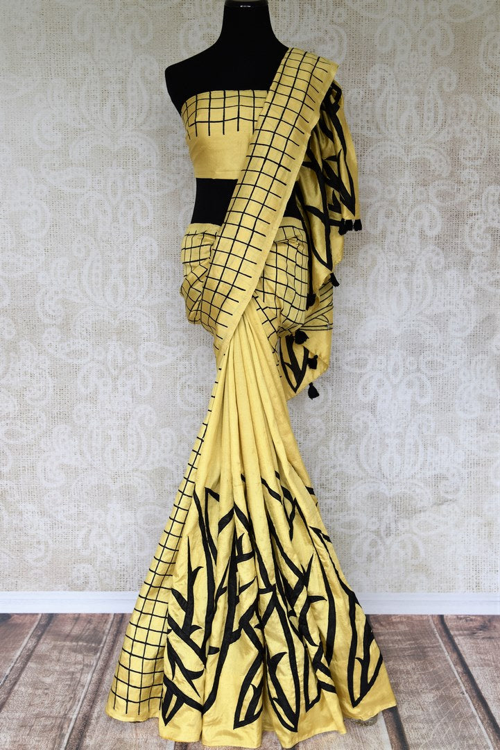Unfold the ecstatic you in our designer gold and black contemporary silk saree. The applique work enhances the beauty of this saree complimented with a gold and black blouse. Style this sari for parties and weddings. Shop handcrafted silk saris, printed sarees, dresses online or visit Pure Elegance store in the USA.-full view