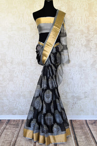 A stunning melange of monochrome hues blend in this designer tribal printed kota silk saree. It comes with gold embroidery detailing on the border with grey and gold blouse. Style it to art fairs, exhibitions, formal events and work. Shop handloom saris, silk sarees, designer saris online or visit Pure Elegance, USA. -full view