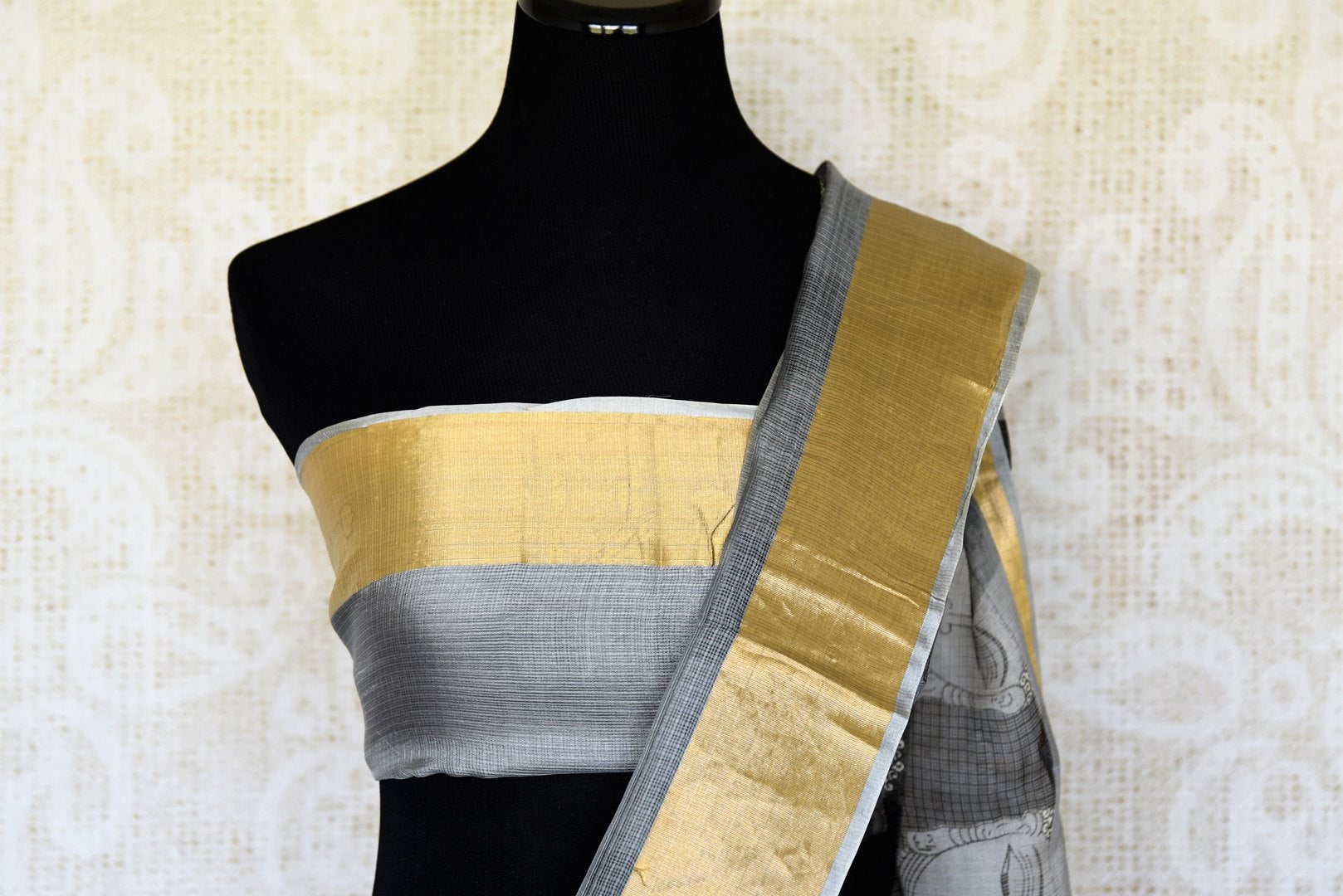 A stunning melange of monochrome hues blend in this designer tribal printed kota silk saree. It comes with gold embroidery detailing on the border with grey and gold blouse. Style it to art fairs, exhibitions, formal events and work. Shop handloom saris, silk sarees, designer saris online or visit Pure Elegance, USA. -blouse pallu