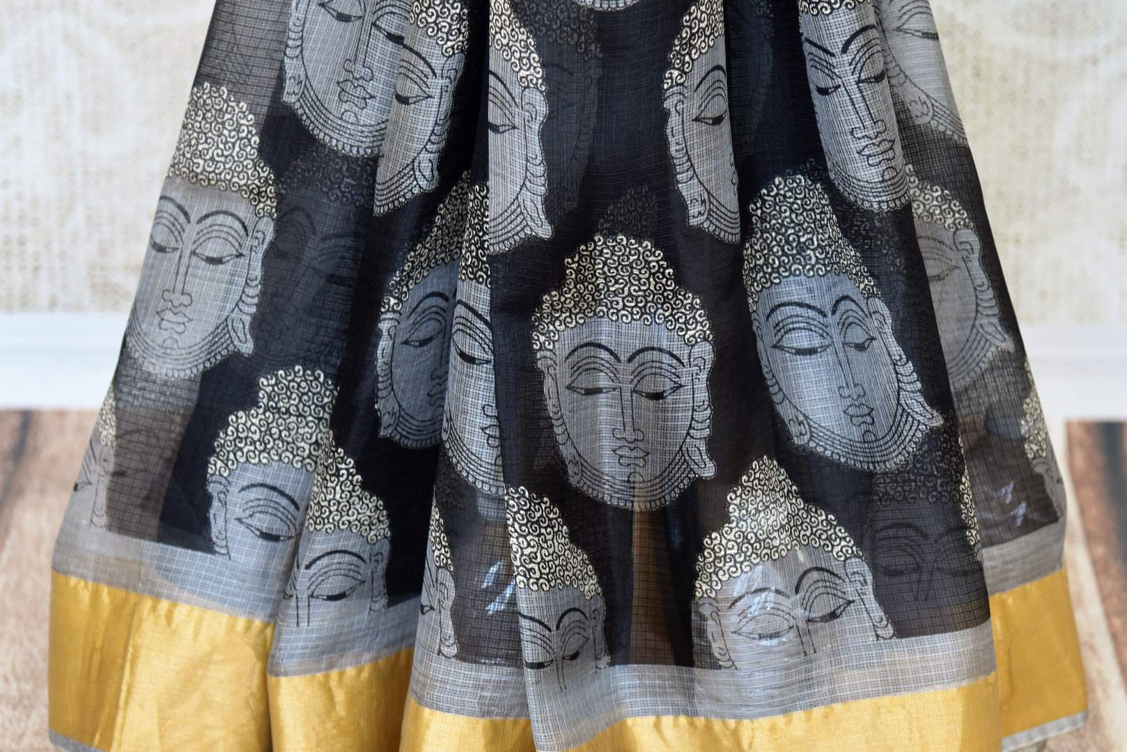 A stunning melange of monochrome hues blend in this designer tribal printed kota silk saree. It comes with gold embroidery detailing on the border with grey and gold blouse. Style it to art fairs, exhibitions, formal events and work. Shop handloom saris, silk sarees, designer saris online or visit Pure Elegance, USA. -pleats