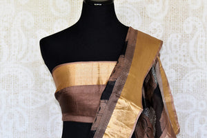 Gorgeous motifs printed on the facade of this black kota silk saree is drool-worthy. The spectacular gold border on border and brown blouse is work of art. You cannot go wrong in this Lord Buddha printed kota silk sari to work.Shop handloom sarees, ikkat saris, printed sarees online or visit Pure Elegance store, USA. -blouse pallu