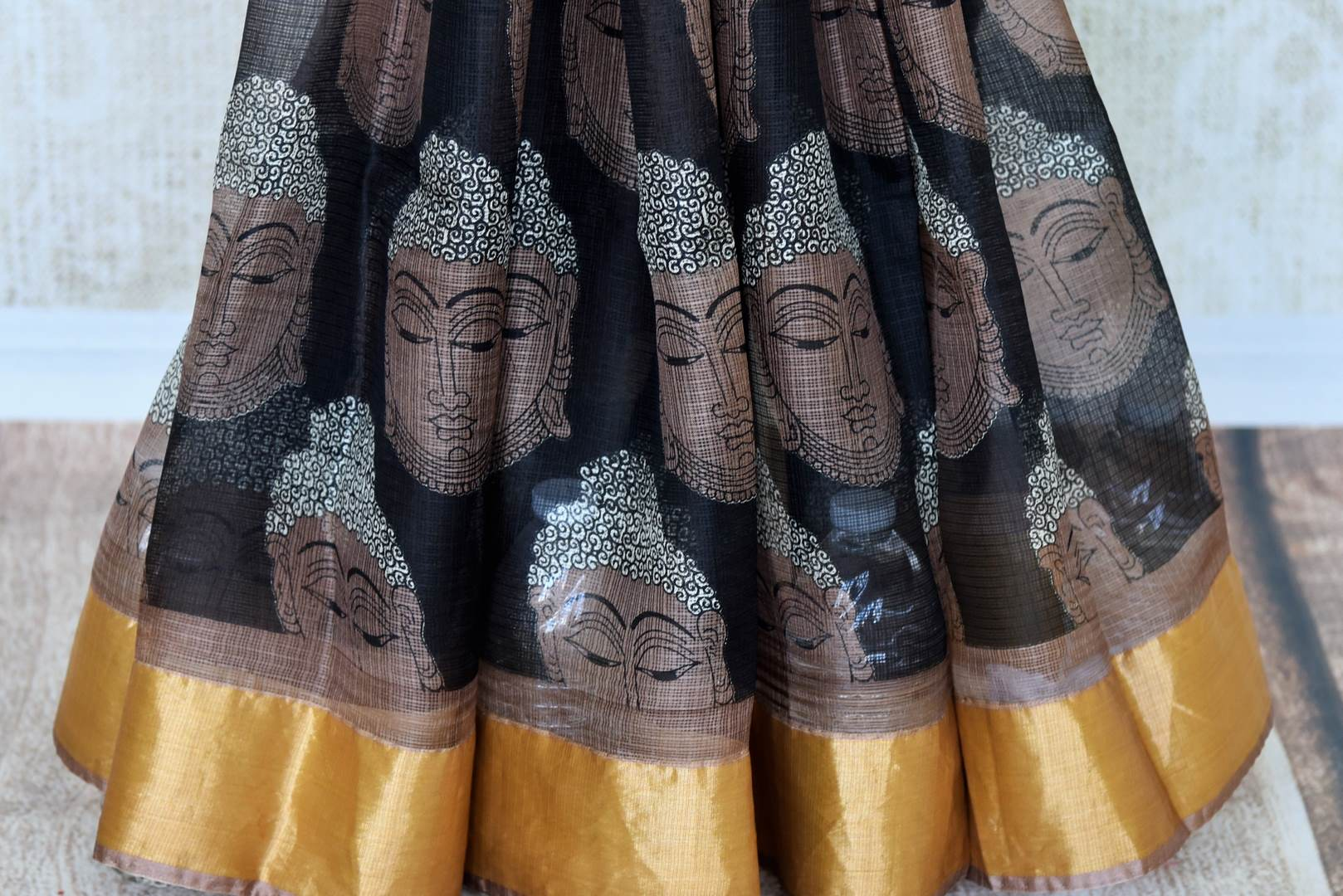 Gorgeous motifs printed on the facade of this black kota silk saree is drool-worthy. The spectacular gold border on border and brown blouse is work of art. You cannot go wrong in this Lord Buddha printed kota silk sari to work.Shop handloom sarees, ikkat saris, printed sarees online or visit Pure Elegance store, USA. -pleats