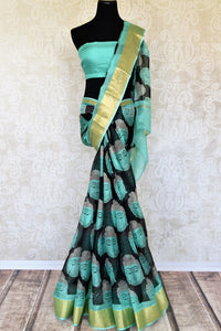 Slay effortlessly in this elegant blue and black zari kota tribal hand printed sari. The gorgeous Lord Buddha's portrait hand printed all over the saree gives quite an artistic expression while the fancy zari border levels up the beauty. Shop silk sarees, ikkat saris online or visit Pure Elegance store in USA. -full view