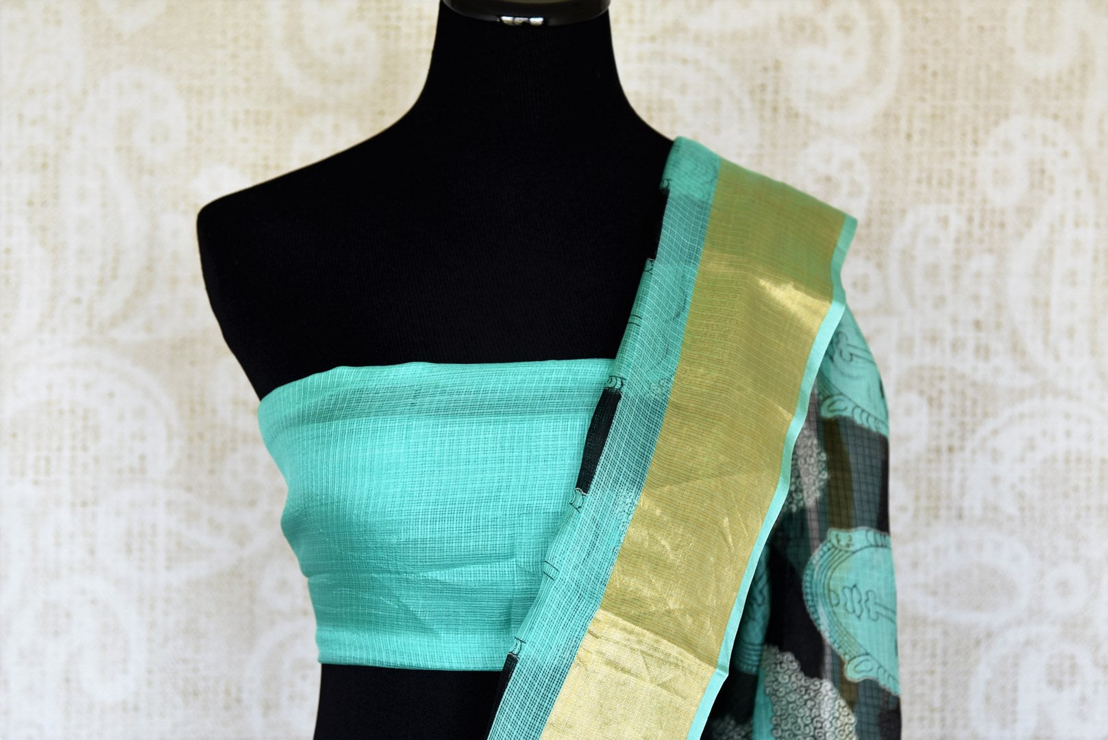 Slay effortlessly in this elegant blue and black zari kota tribal hand printed sari. The gorgeous Lord Buddha's portrait hand printed all over the saree gives quite an artistic expression while the fancy zari border levels up the beauty. Shop silk sarees, ikkat saris online or visit Pure Elegance store in USA. -blouse pallu