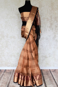 Dreaming hues of brown and gold blend in this organza maheshwari silk sari. Featuring a rich gold zari border with stunning check pattern all over the saree, this is a perfect bet for parties, weddings and events. Shop handcrafted silk sarees, chiffon sari, printed sari online or visit Pure Elegance store, USA.-full view