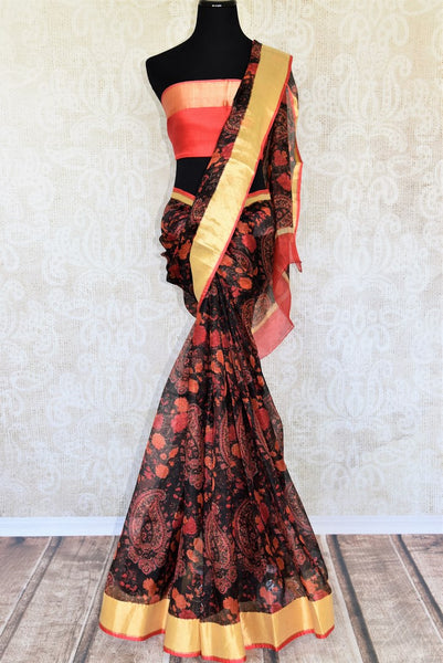 This designer black handprinted kota silk saree is every artistic woman's dream come true. This black and red-hued sari features traditional prints and a contrasting red with zari detailing blouse is spell-binding. Shop designer silk sarees, banarsi silk saris, ikkat sarees online or visit Pure Elegance store, USA. -full view
