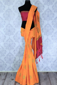 Escalate your style game with this exquisitely designed orange embroidered muga banarsi silk sari. Pair this stunning saree with pink raw silk and embroidered blouse complemented with purple border and embroidery. Shop designer silk sarees, printed saris, banarsi saris online or visit Pure Elegance store in USA. -full view