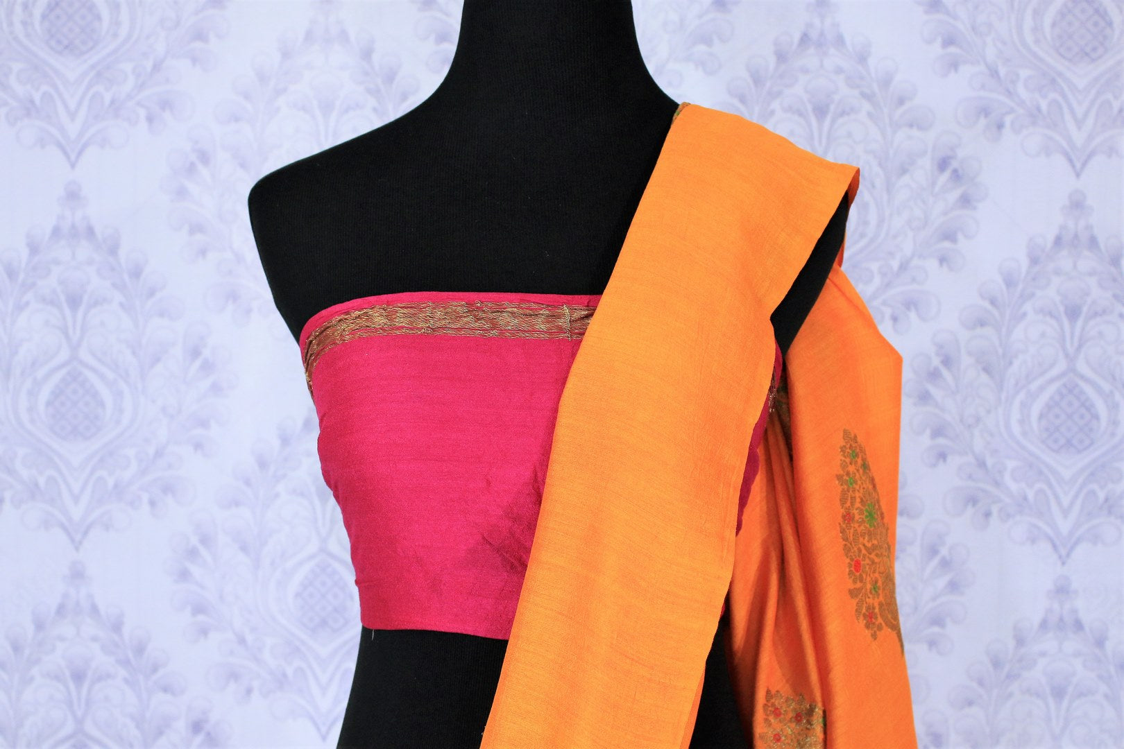 Escalate your style game with this exquisitely designed orange embroidered muga banarsi silk sari. Pair this stunning saree with pink raw silk and embroidered blouse complemented with purple border and embroidery. Shop designer silk sarees, printed saris, banarsi saris online or visit Pure Elegance store in USA. -blouse pallu