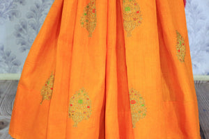 Escalate your style game with this exquisitely designed orange embroidered muga banarsi silk sari. Pair this stunning saree with pink raw silk and embroidered blouse complemented with purple border and embroidery. Shop designer silk sarees, printed saris, banarsi saris online or visit Pure Elegance store in USA. -pleats