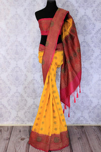Your perfect wedding ensemble in traditional yellow and red combination with zari detailing is oh so dreamy. Indulge in this breath-taking muga banarsi silk saree complemented with a heavy woven red pallu and designer red blouse. Shop designer silk sarees, ikkat sarees online or visit Pure Elegance store in USA.-full view