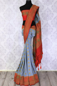 Generously tailored for women with substance, this grey designer muga banarsi silk saree is perfect for weddings and festivities. It comes with a zari border and contrasting red designer blouse and a woven pallu. Shop designer silk saris, ikkat sarees, printed saris online or visit Pure Elegance store in USA. -full view