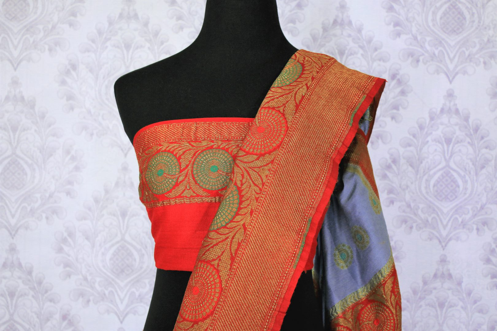 Generously tailored for women with substance, this grey designer muga banarsi silk saree is perfect for weddings and festivities. It comes with a zari border and contrasting red designer blouse and a woven pallu. Shop designer silk saris, ikkat sarees, printed saris online or visit Pure Elegance store in USA. -blouse pallu
