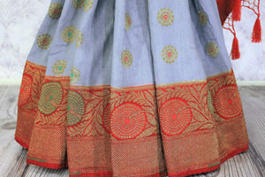 Generously tailored for women with substance, this grey designer muga banarsi silk saree is perfect for weddings and festivities. It comes with a zari border and contrasting red designer blouse and a woven pallu. Shop designer silk saris, ikkat sarees, printed saris online or visit Pure Elegance store in USA. -pleats