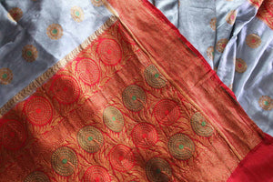 Generously tailored for women with substance, this grey designer muga banarsi silk saree is perfect for weddings and festivities. It comes with a zari border and contrasting red designer blouse and a woven pallu. Shop designer silk saris, ikkat sarees, printed saris online or visit Pure Elegance store in USA. -details
